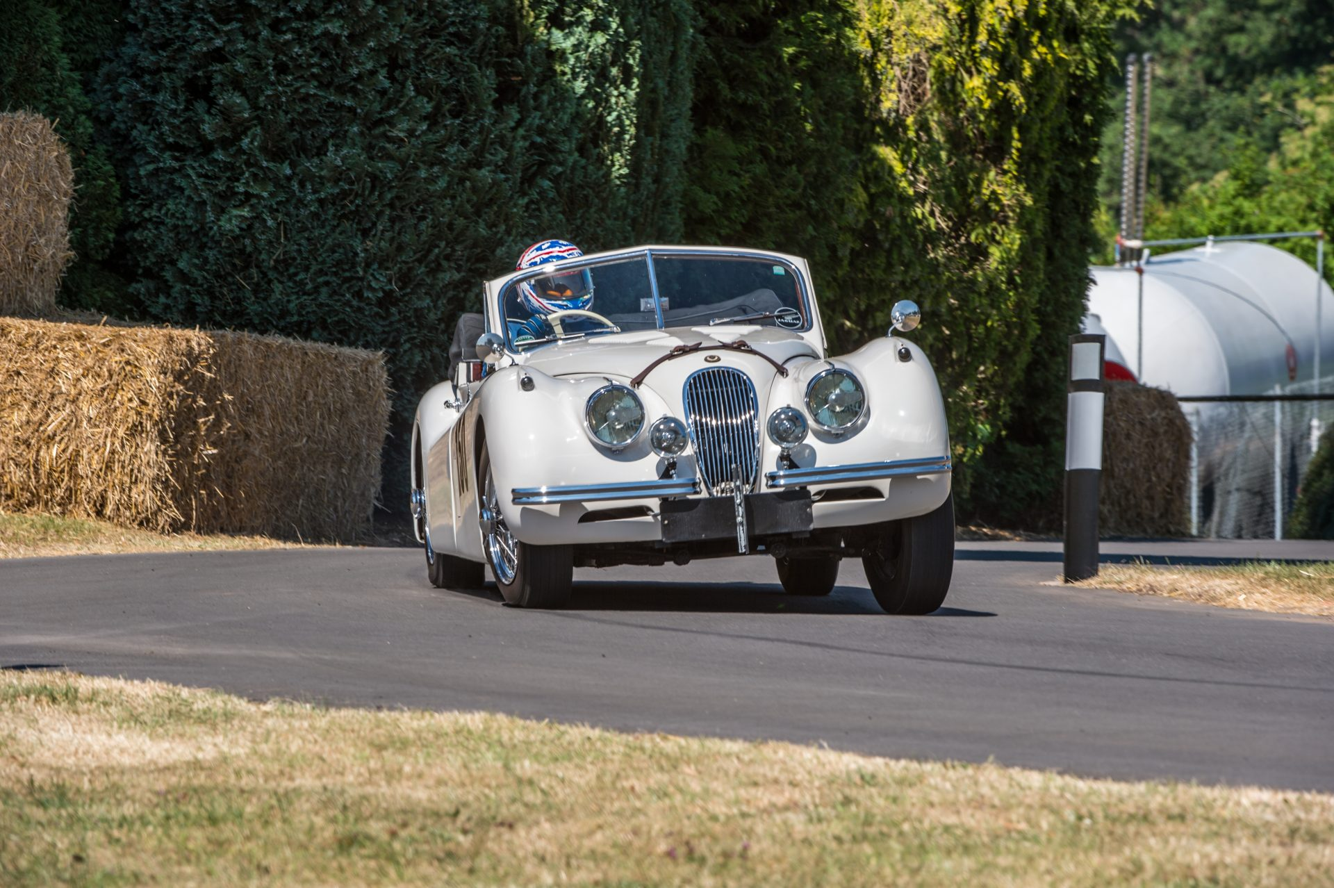 A photo of a white Jaguar XK cornering at the Chateau Impney Hill Climb 2018 where our Classic Car Finance team were in attendance.