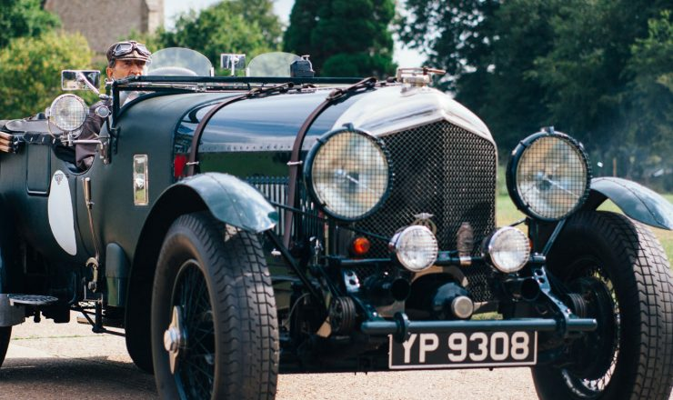 A banner image of a green vintage car with flared wheel arches and two large headlights.