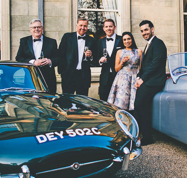 Classic Car Finance team image, 2 classic cars and 6 people.
