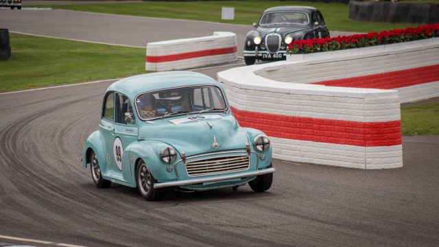 A photo of a blue classic Morris Minor racing in the Jack Sears Memorial Race at the Silverstone classic event which was attended by our classic car finance team.