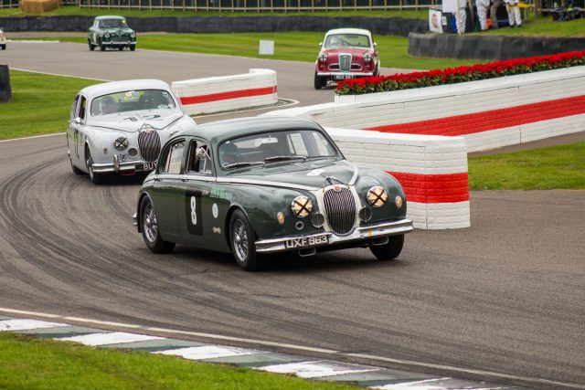 A photo of a grey classic Mark 1 Jaguar racing in the Jack Sears Memorial Race at the Silverstone classic event which was attended by our classic car finance team.