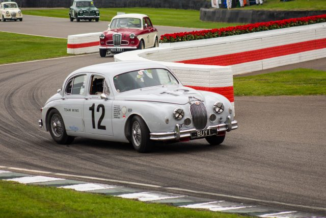 A photo of a white classic Mark 1 Jaguar racing in the Jack Sears Memorial Race at the Silverstone classic event which was attended by our classic car finance team.
