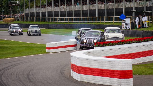 A photo of a blue classic Jaguar racing in the Jack Sears Memorial Race at the Silverstone classic event which was attended by our classic car finance team.