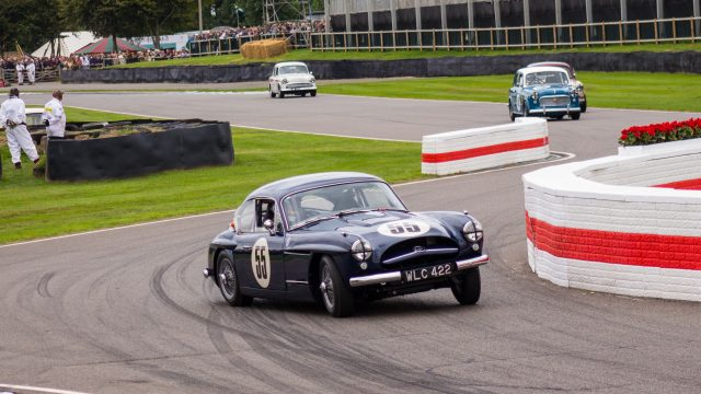 A photo of a blue classic Jaguar XK racing in the Jack Sears Memorial Race at the Silverstone classic event which was attended by our classic car finance team.