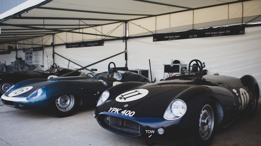 A photo of two classic cars in a garage at the Silverstone Classic race event which was attended by our classic car finance team.