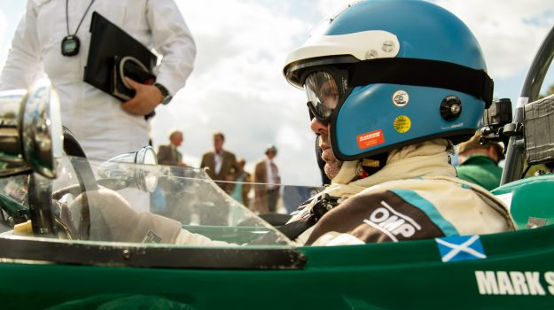 A photo of a racing driver with a blue helmet sat in a green classic race car at the Goodwood Revival which was attended by our classic car finance team.