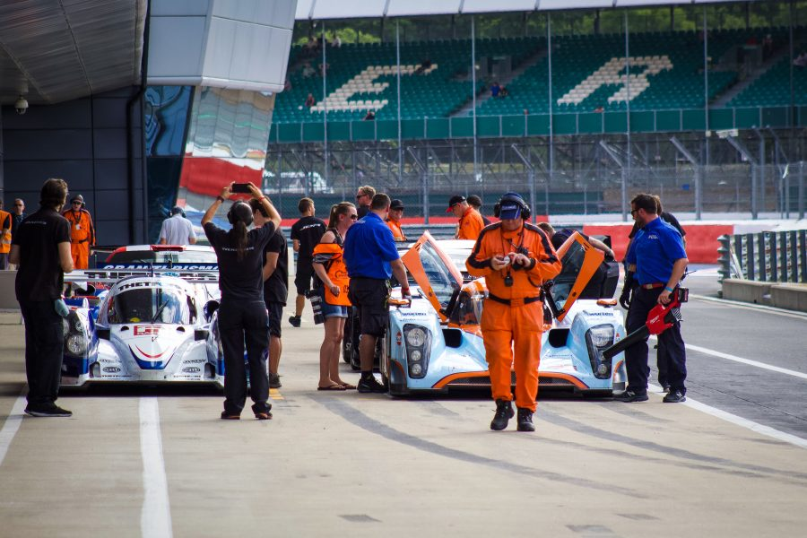 Image of the pitlane at the Silverstone Classic with two EX257 race cars & Pit Crews.