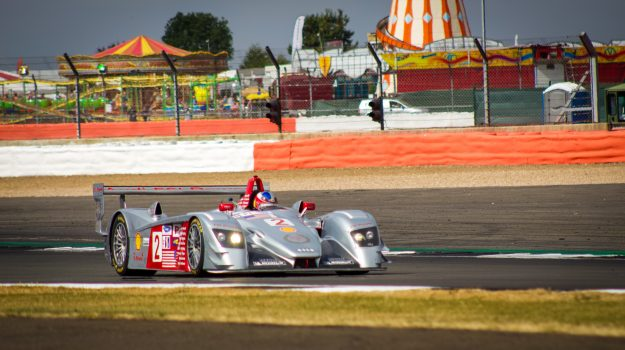 A photo of a Silver & Red Aston Martin race car at the Silverstone classic 2018 event that was attended by our classic car finance team.