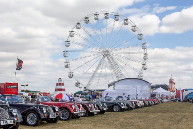 A photo of the car park area at the Goodwood revival event with several classic cars on display.