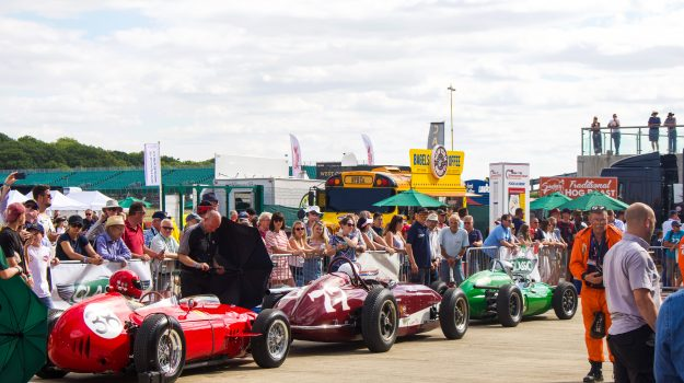 Paddock at the Silverstone Classic, 4 classic race cars are in view. The event was attended by our classic car finance team.