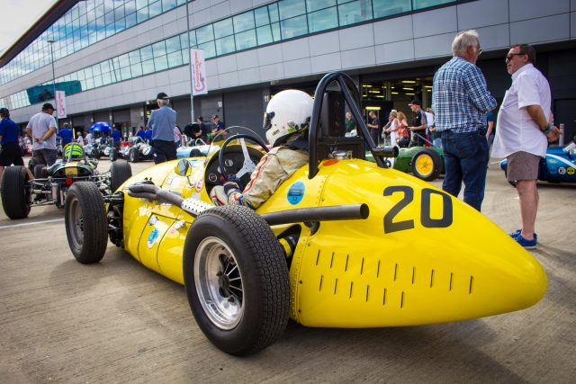 A photo of the Goodwood Revival Sussex Trophy Race Grid with 1 yellow classic race car in view. The event was attended by our classic car finance team.