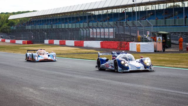 A photo of a two Aston Martin race cars racing at the Silverstone classic 2018 event that was attended by our classic car finance team.