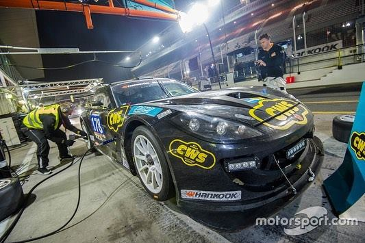 A photo of Angus Fender's black and yellow Ginetta GT5 during a pit stop at the Dubai 24 Hour Race
